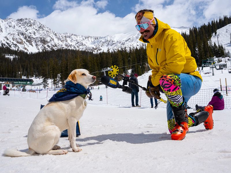 PaddyO interviewing a small dog at the base of a ski area for the parking lot patrol series